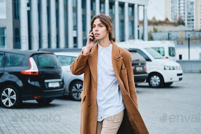 Young beautiful casual woman in coat with cellphone confidently walking through city street