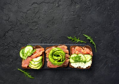 Avocado toast with salmon on rye bread