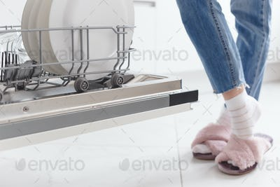 Contemporary housewife: woman standing near dishwasher in the kitchen