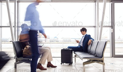 Businessman Sitting In Busy Airport Departure Lounge Using Mobile Phone