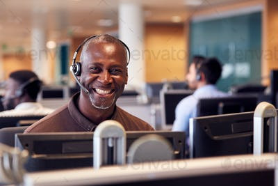 Portrait Of Mature Businessman Wearing Telephone Headset Working In Customer Services Department