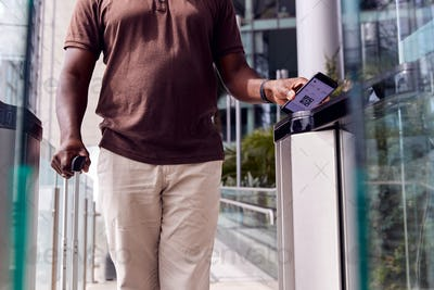 Male Passenger In Airport Departure Lounge Scanning Digital Boarding Pass On Smart Phone