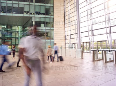 Motion Blur Shot Of Businesspeople In Lobby Of Busy Modern Office