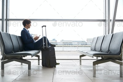 Businessman Sitting In Airport Departure Lounge Using Mobile Phone