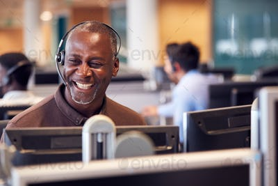 Mature Businessman Wearing Telephone Headset Talking To Caller In Customer Services Department
