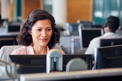 Mature Businesswoman Wearing Telephone Headset Talking To Caller In Customer Services Department