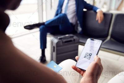 Male Passenger In Airport Departure Lounge Looking At Digital Boarding Pass On Smart Phone