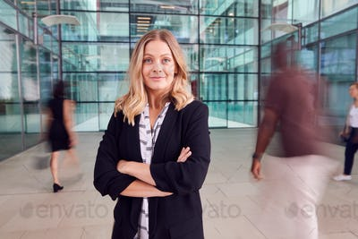 Portrait Of Businesswoman With Crossed Arms Standing In Lobby Of Busy Modern Office