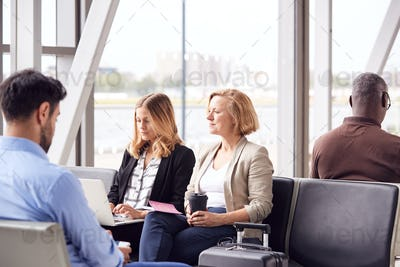 Businesswomen Sitting In Airport Departure Working On Laptop And Drinking Coffee