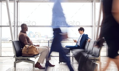 Business Passengers Sitting In Busy Airport Departure Lounge Using Mobile Phones