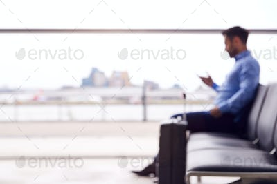Defocused View Of Businessman Sitting In Airport Departure Lounge Using Mobile Phone