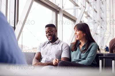 Business Couple Sitting By Window Waiting In Airport Departure Lounge