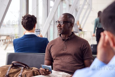 Male Passenger Sitting In Airport Departure Lounge Holding Passport