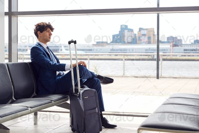 Businessman With Luggage Sitting In Airport Departure Lounge Looking Out Of Window