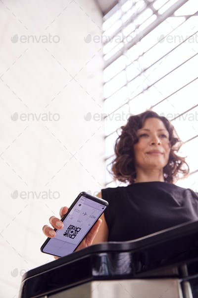 Businesswoman In Airport Departure Lounge Scanning Digital Boarding Pass On Smart Phone