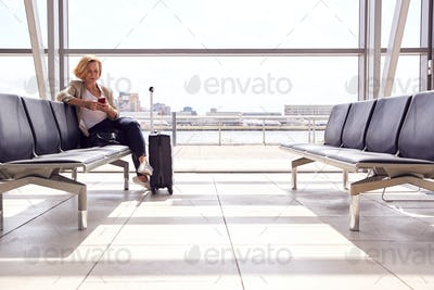 Mature Businesswoman Sitting In Airport Departure Lounge Using Mobile Phone