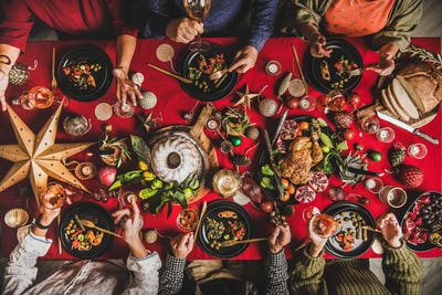 Flat-lay of friends eating and talking at festive Christmas table