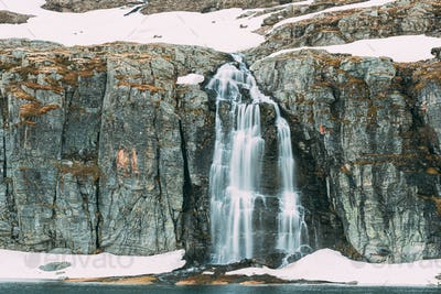 Road Aurlandsfjellet, Norway. Waterfall Flotvatnet In Spring Sno