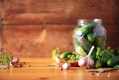 Ingredients, spices and herbs for canning cucumbers over wooden background. Copy space. Dill flowers