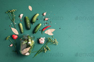 Marinated pickled cucumbers with herbs and spices over green background. Copy space. Top view