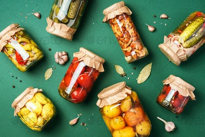 Canned and preserved vegetables in glass jars over green background. Top view. Flat lay. Copy space