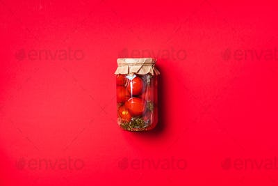 Pickled tomatoes in jar on red background. Top view. Flat lay. Copy space. Canned and preserved