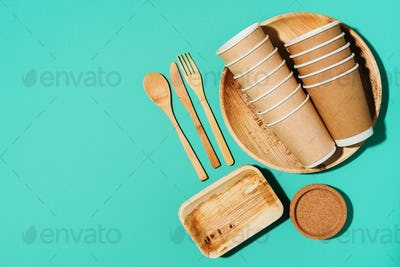 Disposable tableware from natural materials. Bamboo plates, wooden spoon, fork, knife, craft paper