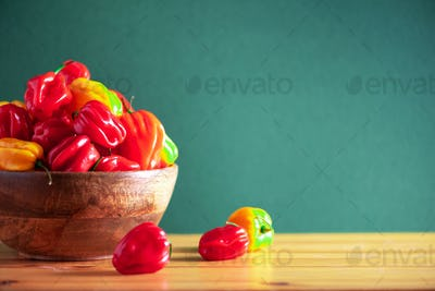 Colorful scotch bonnet chili peppers in wooden bowl over green background. Copy space