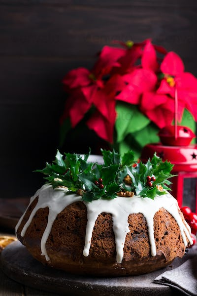 Christmas chocolate cake with white icing and pomegranate kernels on a wooden dark background with