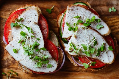 Sandwiches with turkey meat and fresh vegetables served with microgreens on a wooden plate