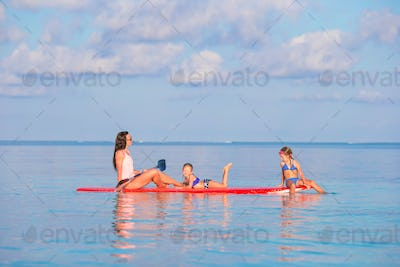 Mother and little girls on surfboard during summer vacation