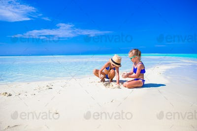 Adorable little girls on beach during summer vacation