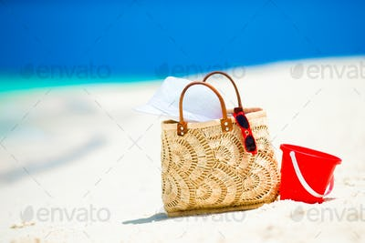 Beach accessories - straw bag, white hat and red sunglasses on the beach