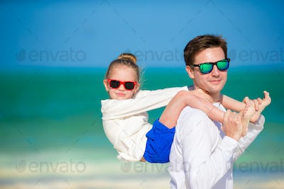 Little girl and father at tropical beach having fun