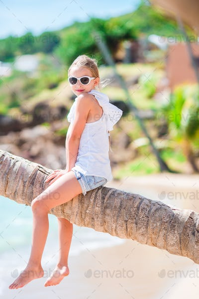 Adorable little girl at tropical beach sitting on palm tree during summer vacation