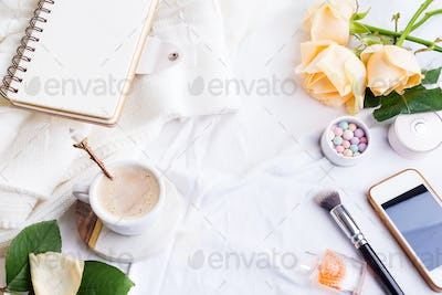Phone, white cup of coffee and roses with notebook on white bed and plaid, cozy morning light