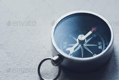Small magnetic compass on a grey background