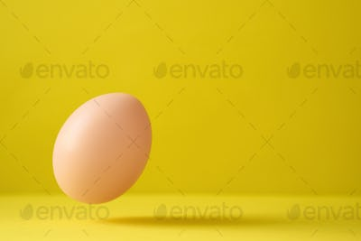 Egg Falling Down On Yellow Background