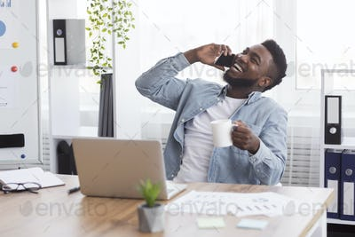 Joyful african businessman talking on phone and drinking coffee at workplace