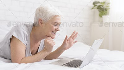 Cheerful grandmother talking with relatives via digital tablet online