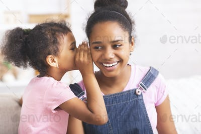 Playful african sister whispering secrets at home