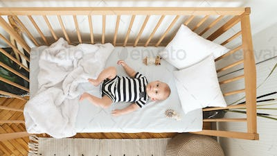 Curious newborn baby lying in crib and looking at camera