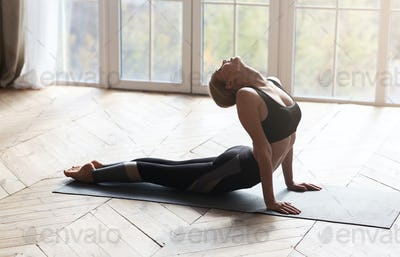 Athletic young woman making cobra pose, exercising in studio