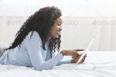 Beautiful afro girl serfing internet on digital tablet