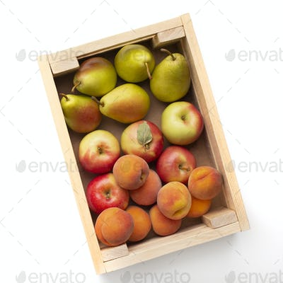 Fresh and organic garden fruits in eco wooden box on white