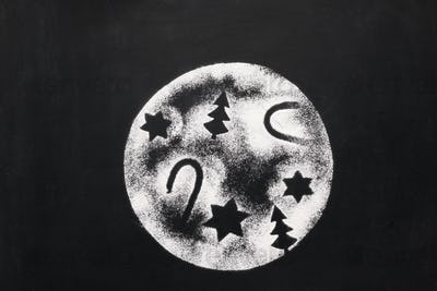 Moon with holiday figures of sugar on chalkboard