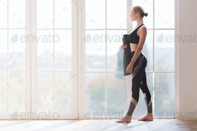 Woman before practicing yoga, holding yoga mat at studio