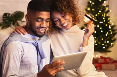 Christmas holiday. African-american couple choosing gifts on tablet