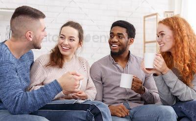 Joyful friends drinking tea and talking at home