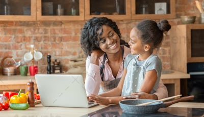 Mommy and daughter embracing, reading recipe on laptop at kitchen